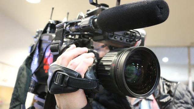 Un cameraman tient une caméra.