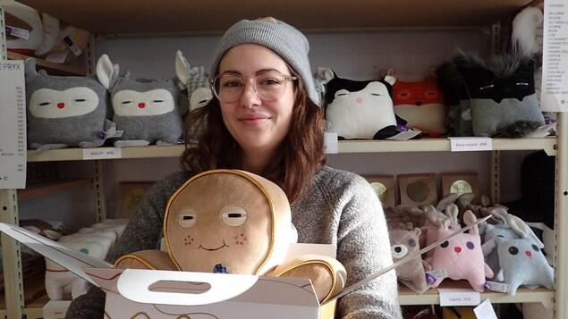 Une femme tient dans ses bras une boîte ouverte avec un coussin en forme de pain d'épice