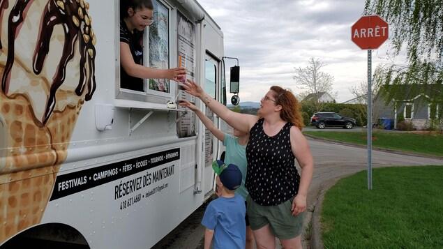 Une employée de la Chocolaterie Beljade remet une coupe glacée à une mère et ses deux enfants.