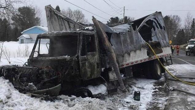 Un camion complètement incendié après une collision.