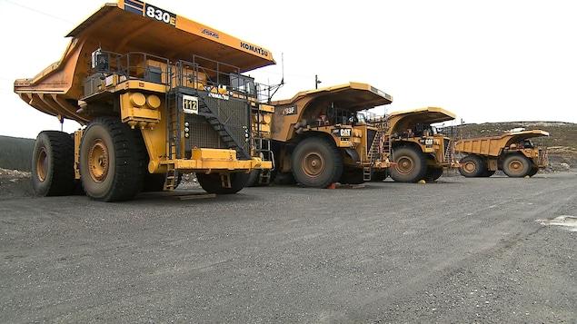 Quatre camions à benne basculante stationnés à la mine du Lac Bloom, près de Fermont.