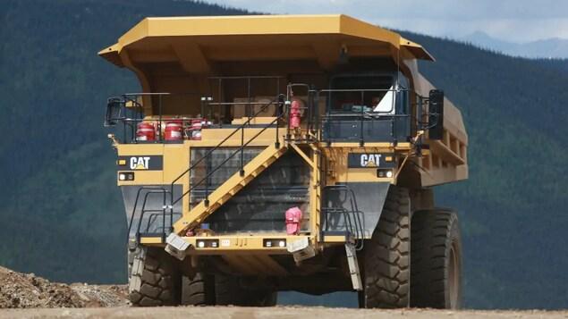 Un énorme camion de la mine Eagle est garé sur un chemin avec, derrière lui, une forêt.