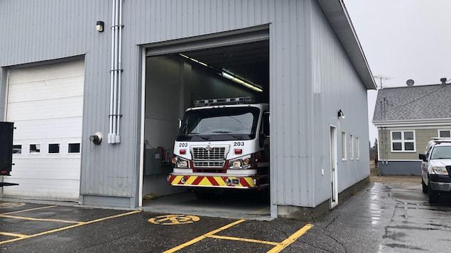Un camion de pompier stationné dans un garage sous la pluie à Longue-Pointe-de-Mingan.