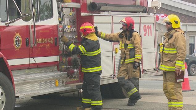Des pompiers à côté de leur camion.
