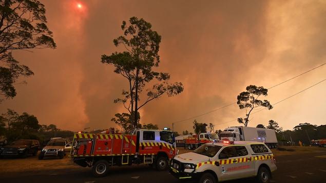 Des véhicules d'intervention et des camions de pompiers devant un panache de fumée qui voile partiellement le soleil.