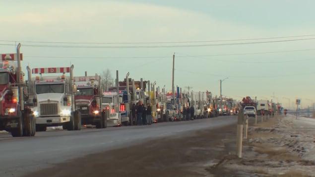 Une longue file de camions circule sur une autoroute.