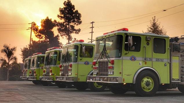 Cinq camions de pompiers alignés sous un ciel enfumé