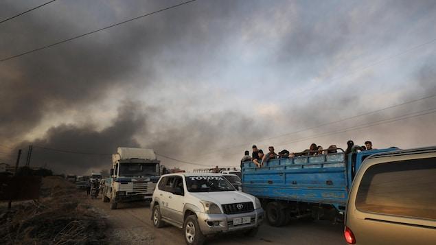 Un convoi de camions et de camionnettes remplis de gens sous un ciel enfumé.