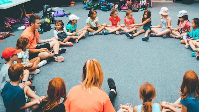 Des enfants et des animateurs qui se tiennent par la main assis en cercle.