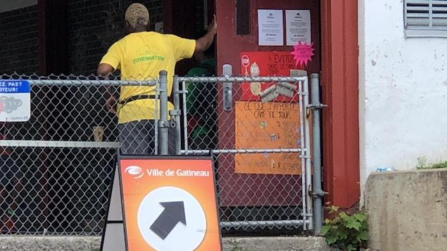 Un employé du camp de dos accueille les enfants devant une pancarte annonçant le camp de jour.