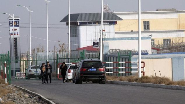 Des gens marchent dans une rue qui mène à un centre de détention.
