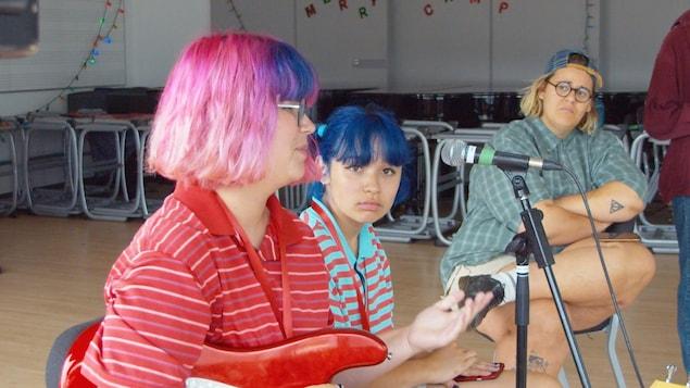 L'artiste regarde des jeunes qui sont au micro avec une guitare.