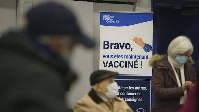 Trois personnes attendent près d'une pancarte où on peut lire : « Bravo, vous êtes maintenant vacciné! »
