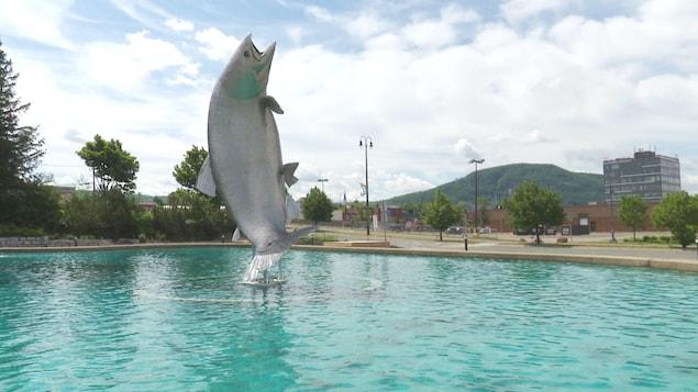 Une statue de poisson dans une fontaine et la montagne en arrière-plan.