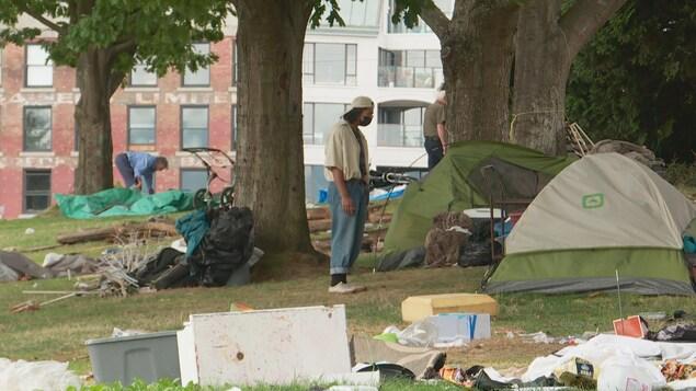 Un homme se tient devant sa tente.
