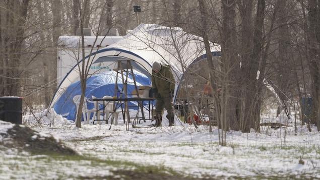 Un homme près d'une toile de protection dressée au-dessus d'une table et de chaises; derrière, on aperçoit une tente bleue et une roulotte sur le terrain enneigé où il y plusieurs arbres.