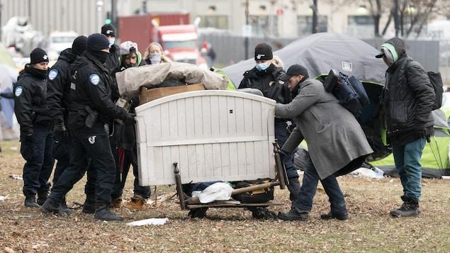 Des policiers déménagent une base de lit.