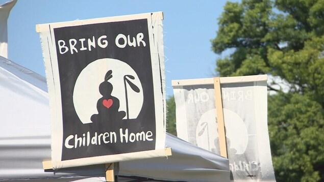 Affiche exposant le nom du campement ainsi que son symbole : un Autochtone assis en tailleur avec un coeur rouge sur la poitrine.