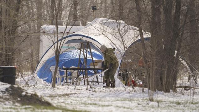 Un homme près d'une tente et une roulotte installées sur un terrain enneigé.