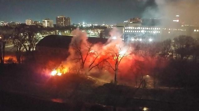 Des flammes et de la fumée entourent le bâtiment du club de curling près de la berge de la rivière, alors qu'il fait encore nuit.