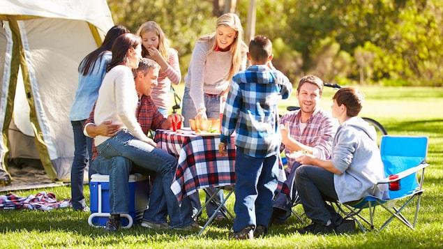 Des amis partagent un repas en camping.