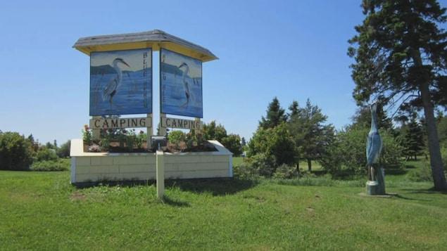 L'entrée d'un camping avec une effigie d'un héron, sur lequel est écrit CAMPING HÉRON BLEU. Paysage estival d'été, ciel bleu et verdure.