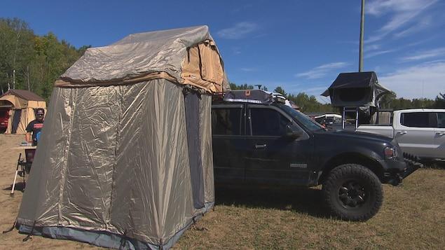 Une tente est installée sur le toit d'un camion dans un stationnement.