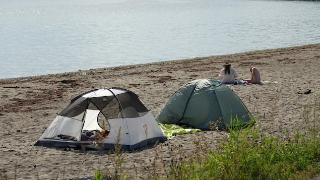 Deux tentes et deux personnes installées sur une plage.