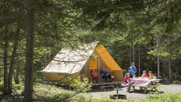 Une tente luxueuse et une famille qui pique-nique dans la forêt.