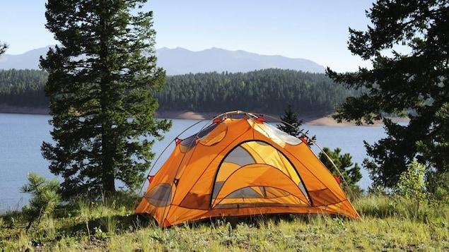 Une tente jaune est installée près d'un lac.