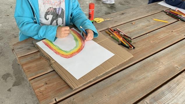 Une jeune fille dessine un arc-en-ciel colorés sur une table à pique-nique, où du matériel de bricolage est disposé.