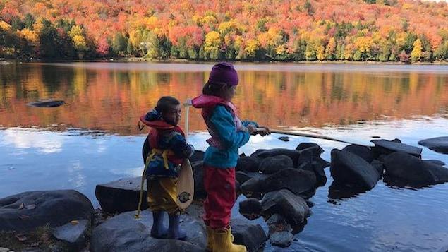 Mélane, 11 ans, et Zakaël, 7 ans, pêchent sur le bord d'un lac
