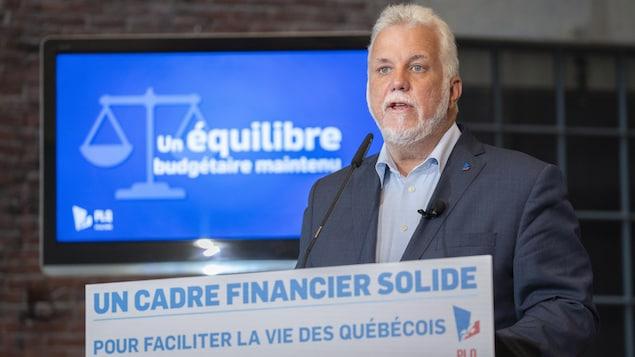 Philippe Couillard devant un lutrin parle dans un micro.