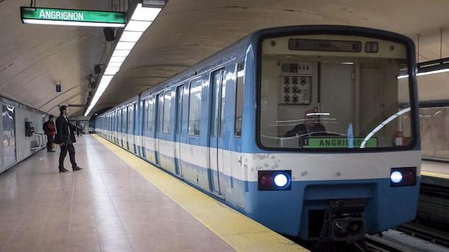 Une rame de métro bleue arrive dans une station.