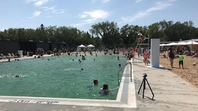 Dans l'image, il y a une partie de la piscine et du terrain de volley-ball. Des gens se baignent dans la piscine.