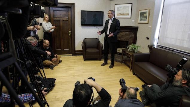 Travis Toews, debout dans son bureau, chaussé de bottes. Des photographes et des caméramans se pressent autour de lui.