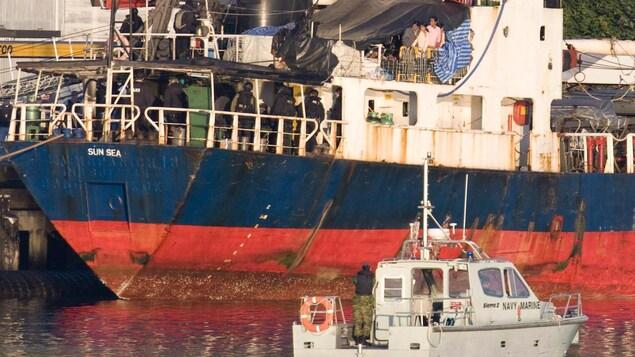 Des policiers de l'escouade spéciale inspectent un navire.