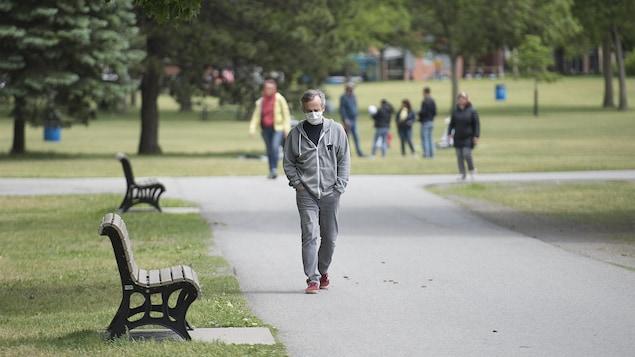 Un homme portant un masque de protection marche dans un parc.