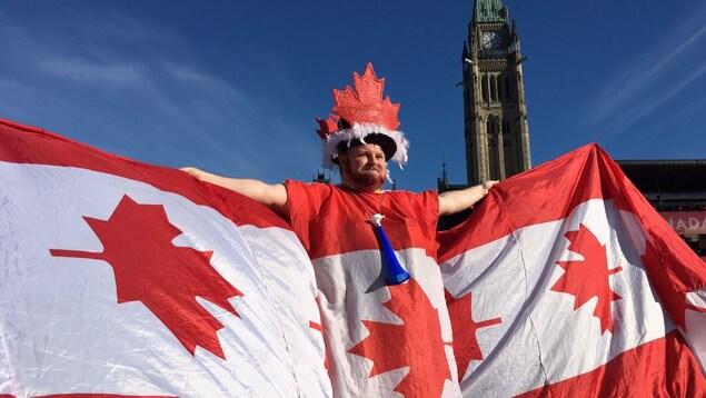 Un homme portant un costume fabriqué à partir de plusieurs drapeaux canadiens à l'occasion du 152e anniversaire de la création du pays.