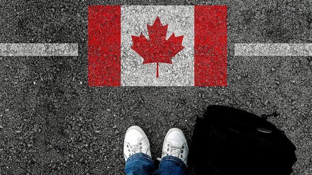 Un drapeau du Canada peint sur l'asphalte avec une ligne horizontale et en bas de l'image les pieds d'une personne debout à côté d'un sac de voyage.