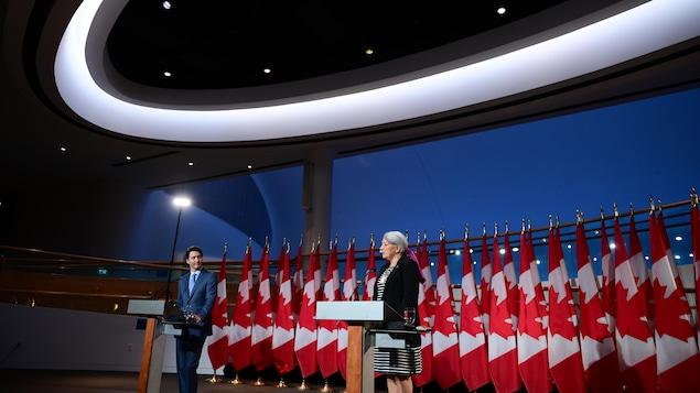 Mary Simon et Justin Trudeau, debout, devant une rangée de drapeaux du Canada, dans une salle éclairée par des projecteurs.