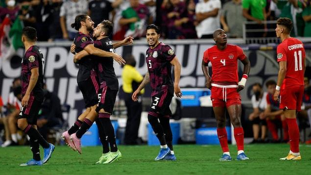 Des joueurs mexicains sont en liesse, alors que des joueurs canadiens semblent découragés.