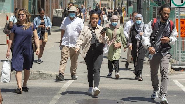 Des passants, certains portant un couvre-visage, déambulent sur la rue Sainte-Catherine à Montréal en juin 2020.