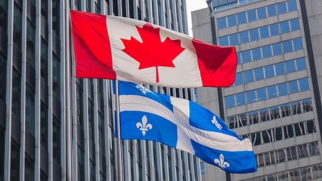 Des drapeaux canadien et québécois au vent.