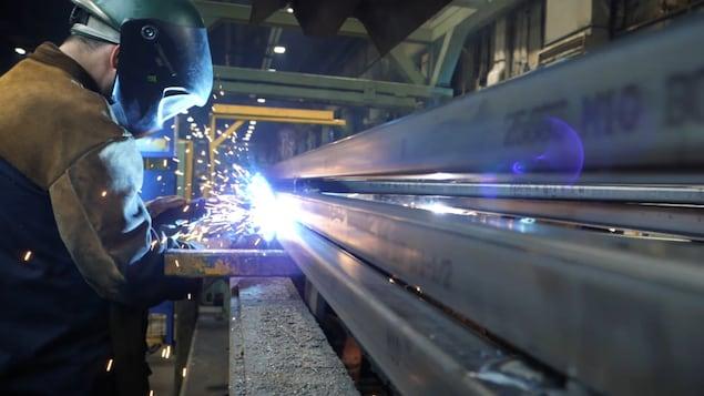 Un homme soude une pièce de métal.