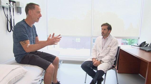 Un médecin assis sur un chaise qui écoute son patient assis sur la table d'examen.