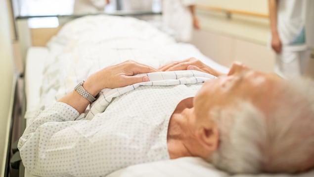 Un homme âgé est allongé sur une civière dans un couloir d'hôpital.