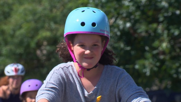 Une jeune fille portant un casque circule à vélo.