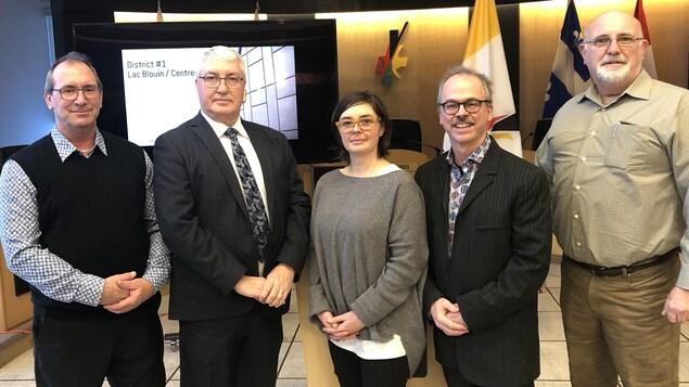 Quatre hommes et une femme posent dans la salle du conseil municipal de Val-d'Or.