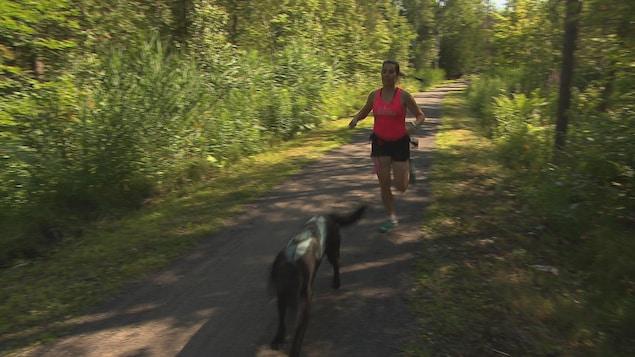 Geneviève Baril en entraînement avec Flair. La labrador noire est attachée à sa maîtresse avec un harnais.